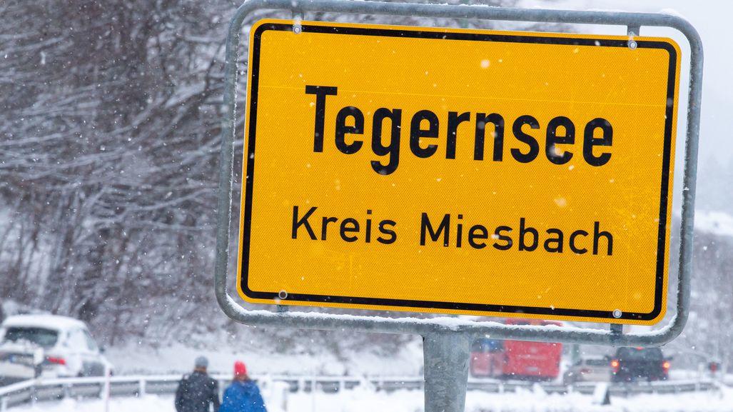 Ortsschild Tegernsee, Landkreis Miesbach mit Spaziergängern