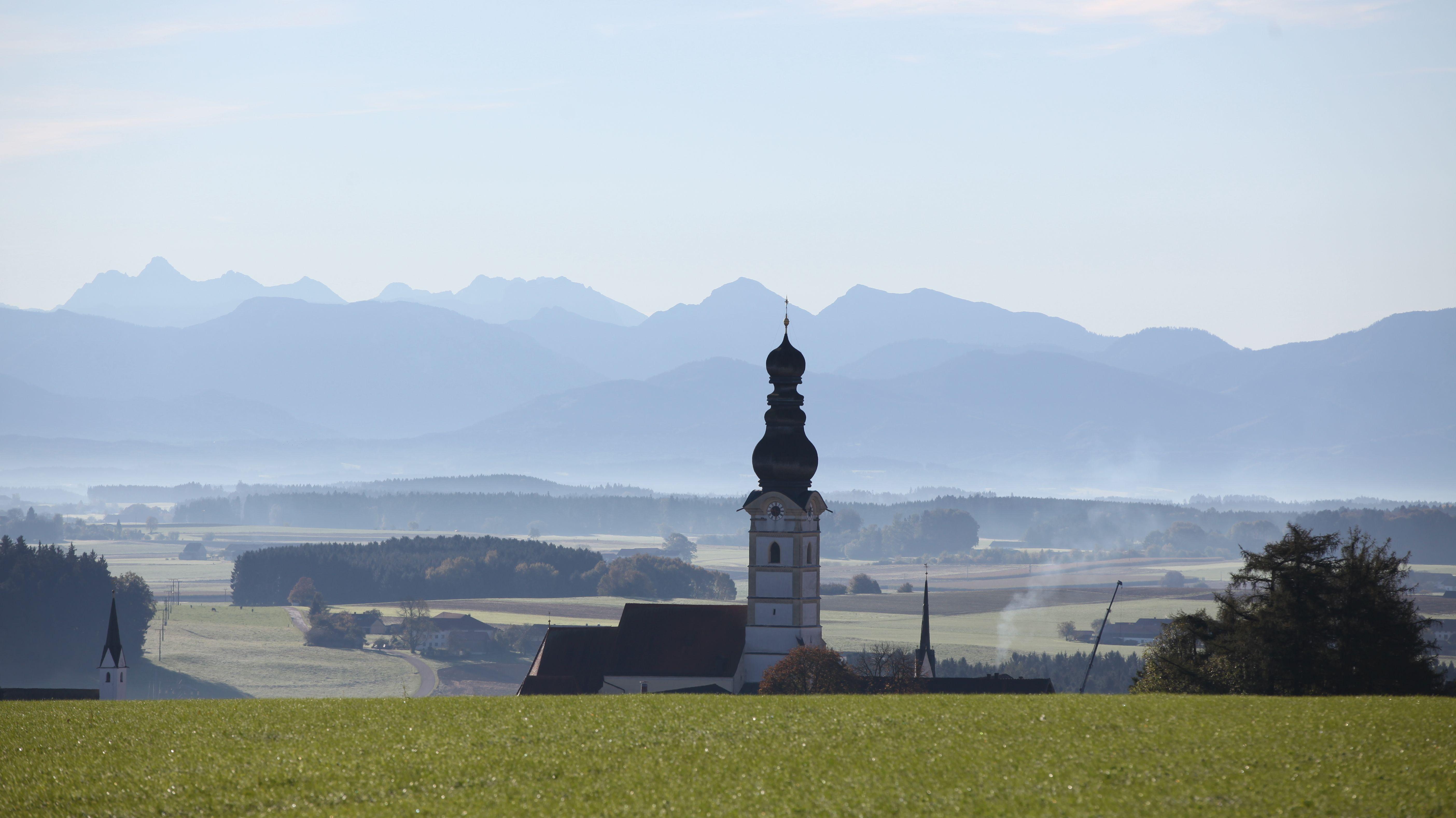 Die Pfarrkirche von Schnaitsee vor dem Alpenpanorama