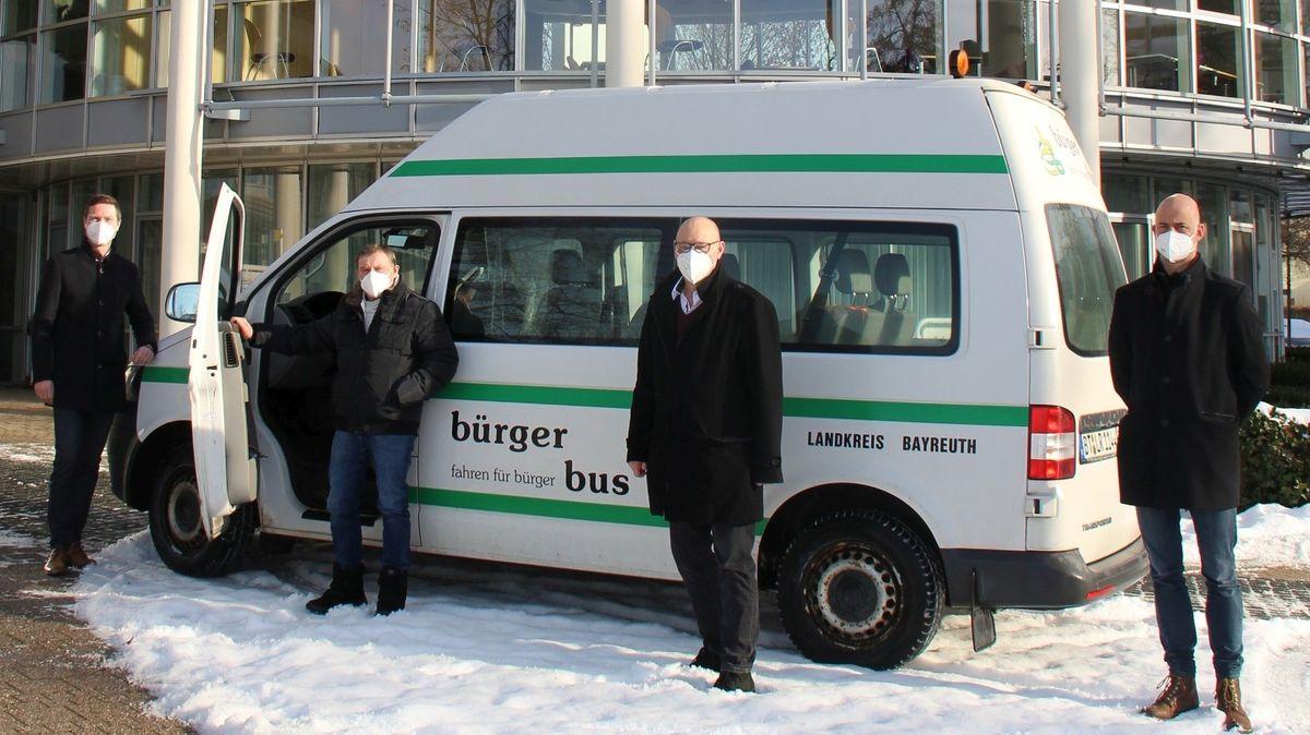 Ein weiß-grüner Bus parkt vor dem Landratsamt, daneben stehen (von links) Landrat Florian Wiedemann, Kreisseniorenbeauftragtet Manfred Neumeister, der Seniorenbeauftragte der Stadt Hollfeld, Michael Schatz, und Max Frankenberger von der Regionalen Entwicklungsagentur des Landkreises.