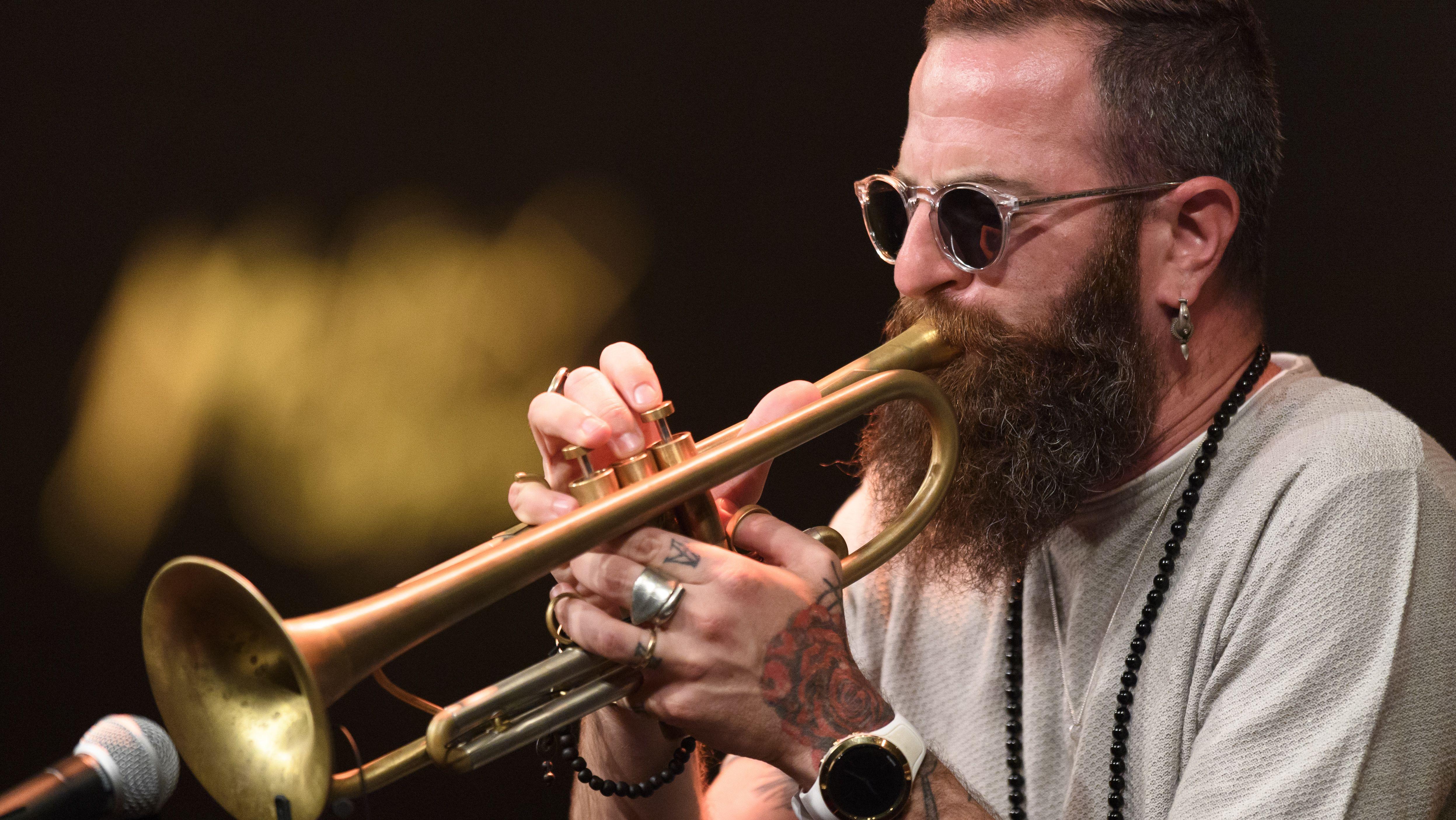 Avishai Cohen bei einem Auftritt an der Trompete. Er trägt Sonnenbrille, Tätowierungen und viele große Ringe.
