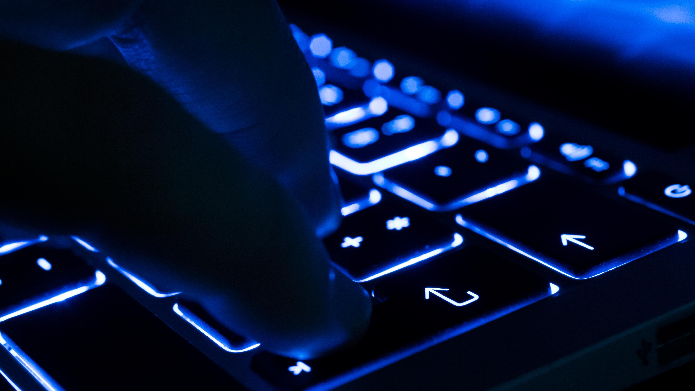 Mann tippt auf beleuchteter Tastatur