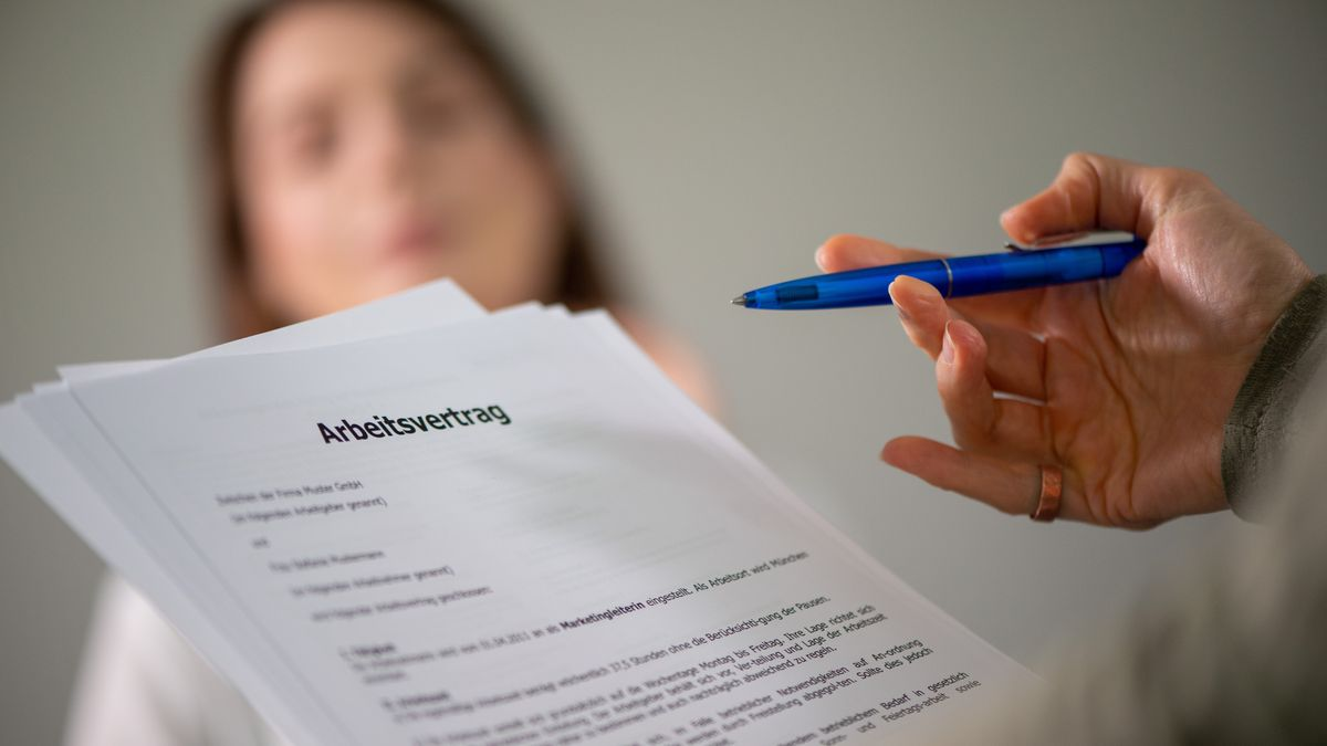 Eine Person hält einen Anstellungsvertrag in de Hand