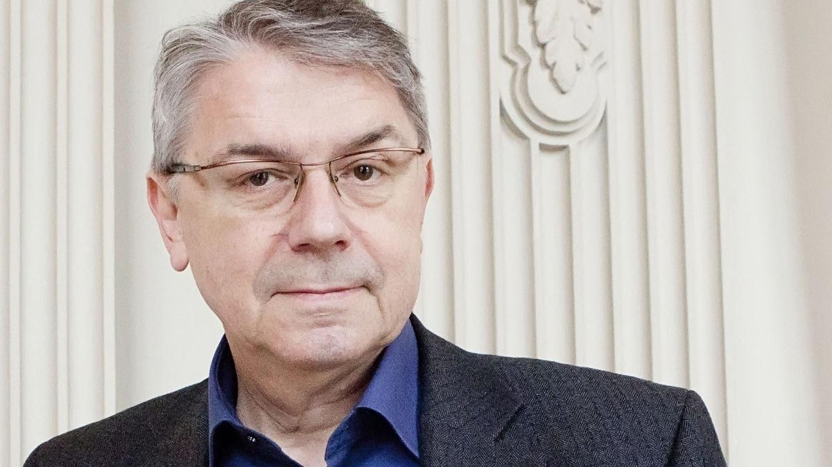 Ulrich Khuon, Präsident des Deutschen Bühnenvereins, blickt vor einer weißen Wand mit Stuck in die Kamera