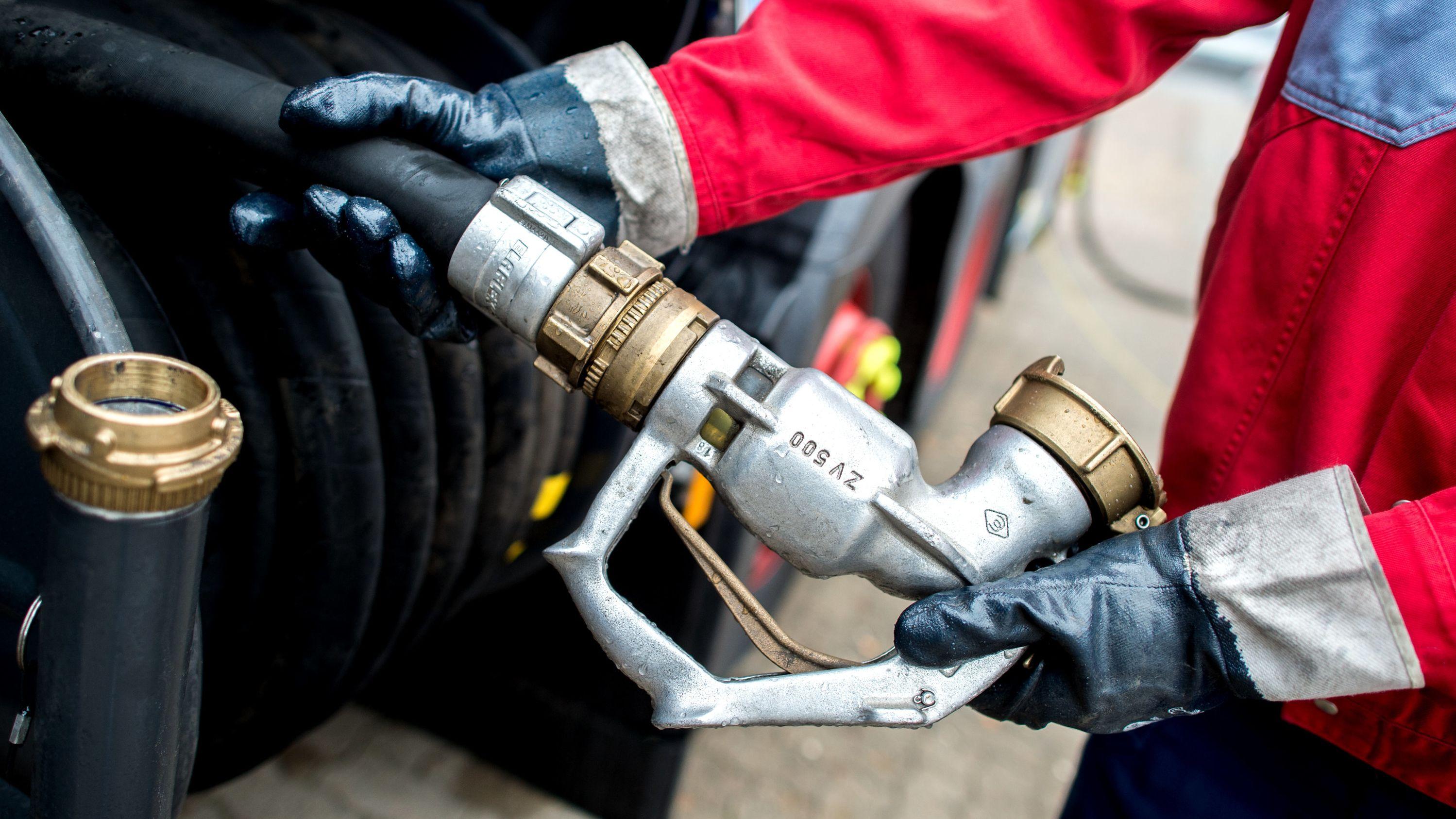 Der Fahrer eines Heizöllieferanten hält die Zapfpistole eines Tanklasters für die Auslieferung von Heizöl in den Händen.