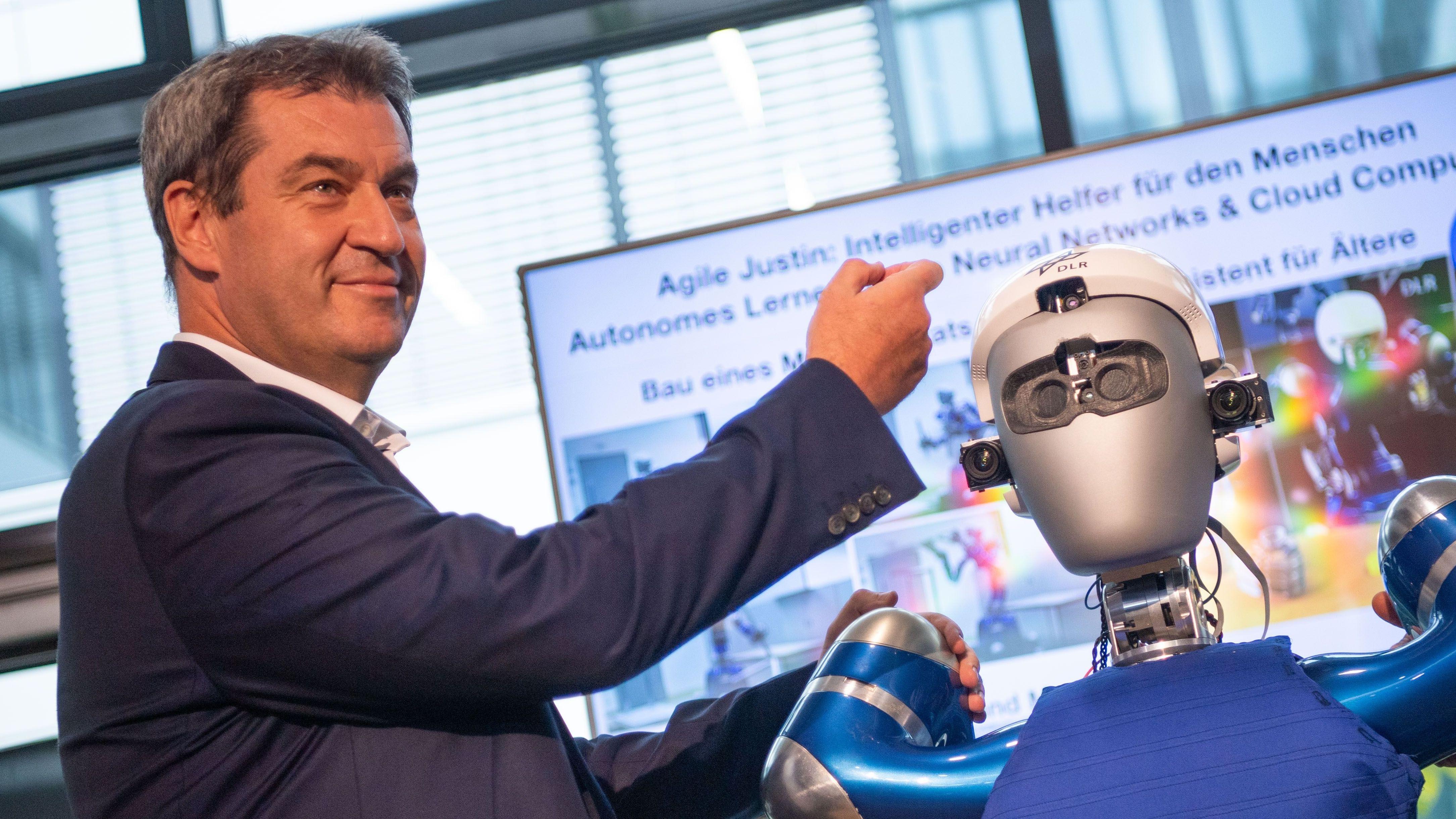 Markus Söder am 6.9. mit einem selbstlernenden Roboterhelfer