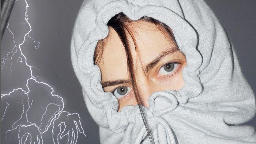 Ein blaugraues Augenpaar und eine dunkle Haarsträhne lugen aus einem zugeknöpften Hoodie hervor.