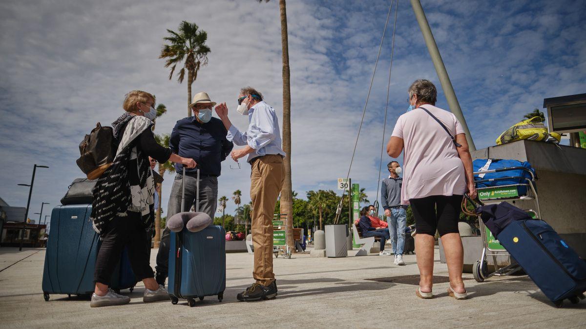 Urlauber auf Teneriffa mit Gepäck und Maske