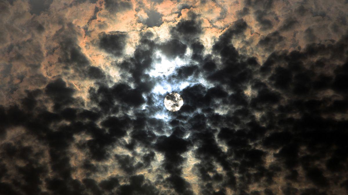 Die Sonne scheint durch sehr dunkle Wolken hindurch