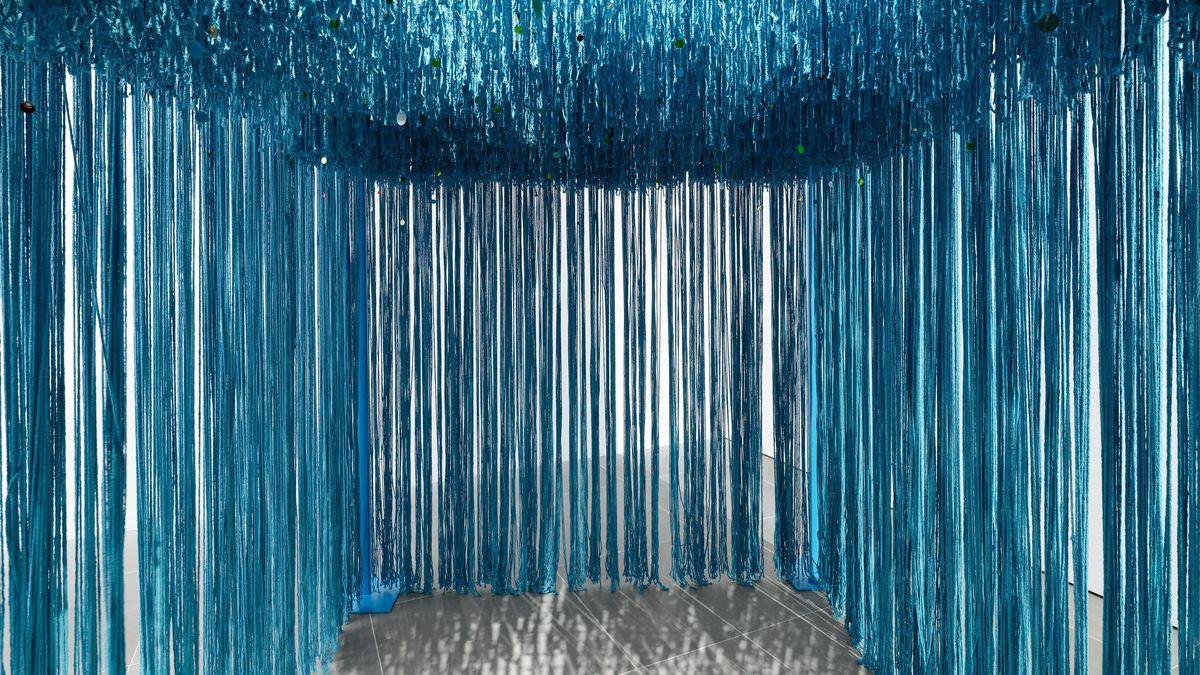 Blaue Fäden hängen von der Decke und schaffen einen Raum im Raum.