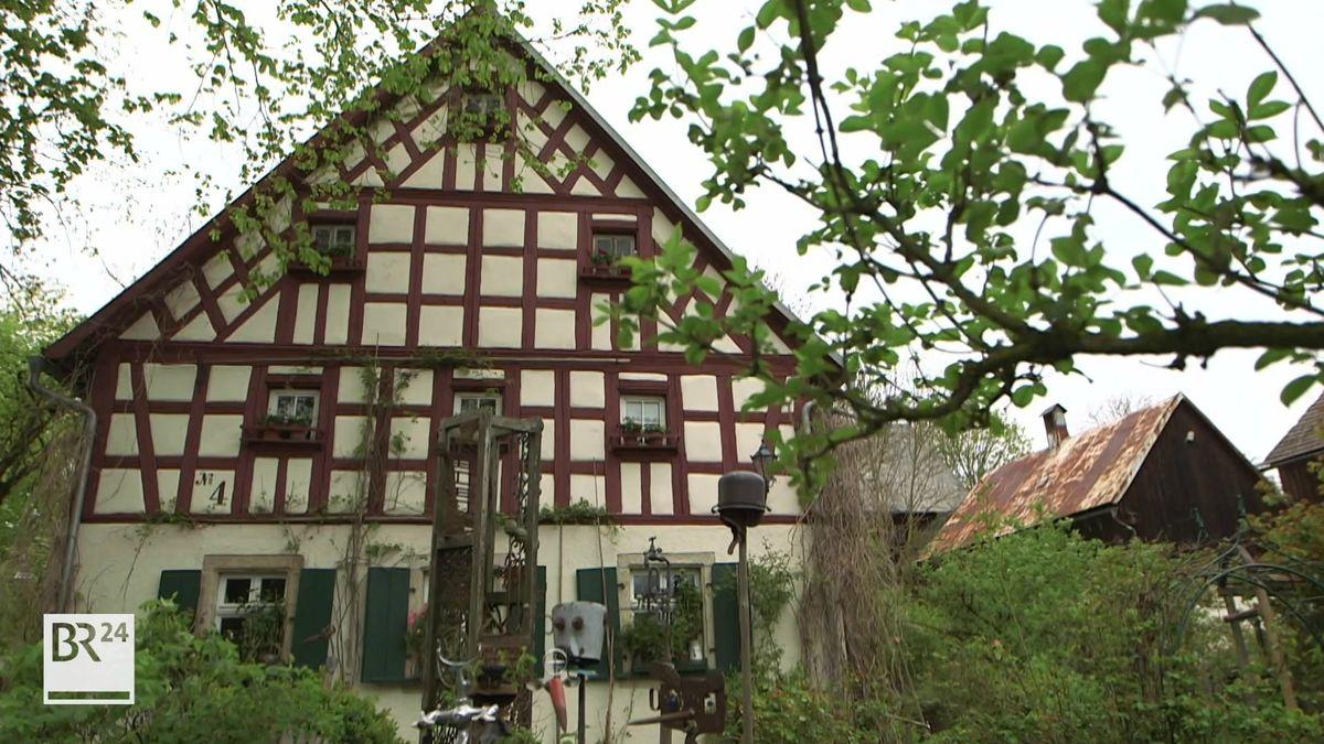 Die Fachwerkfassade des Bauernhauses von Claus Hetterich, das von Bäumen und Sträuchern nahezu eingewachsen ist.