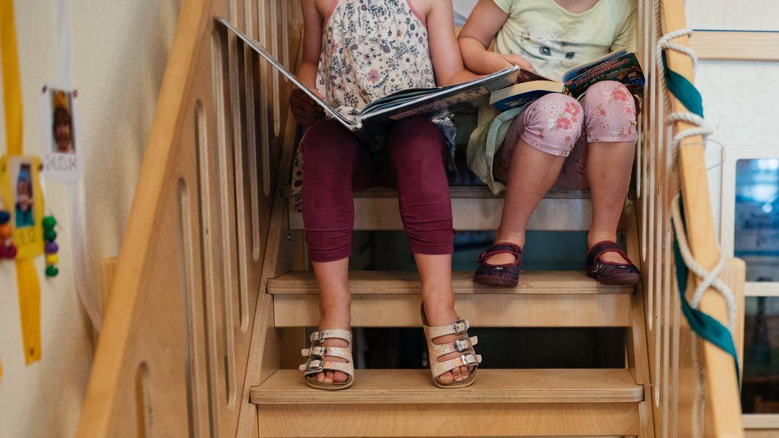 Zwei Mädels sitzen auf einer Treppe und lesen in einem Bilderbuch.