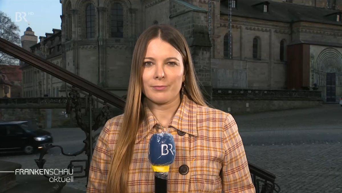 BR-Reporterin Sandra Jozipovic mit einem Mikrophon in der Hand steht vor dem Bamberger Dom.