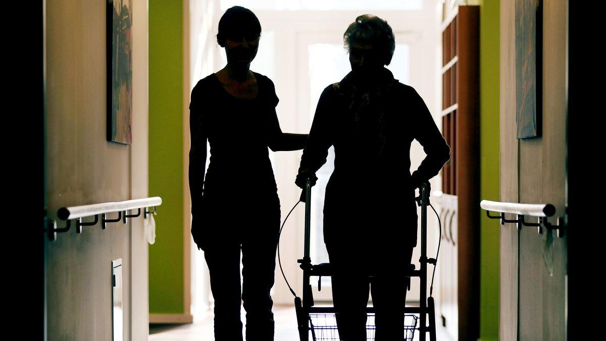 Eine Pflegekraft begleitet Heimbewohnerin über den Flur.