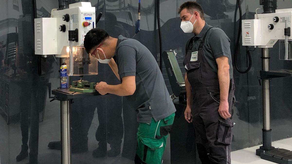 Zwei Männer mit Mundschutz und Arbeitshosen stehen an einer Maschine zur Fertigung von Kunststoffprodukten.