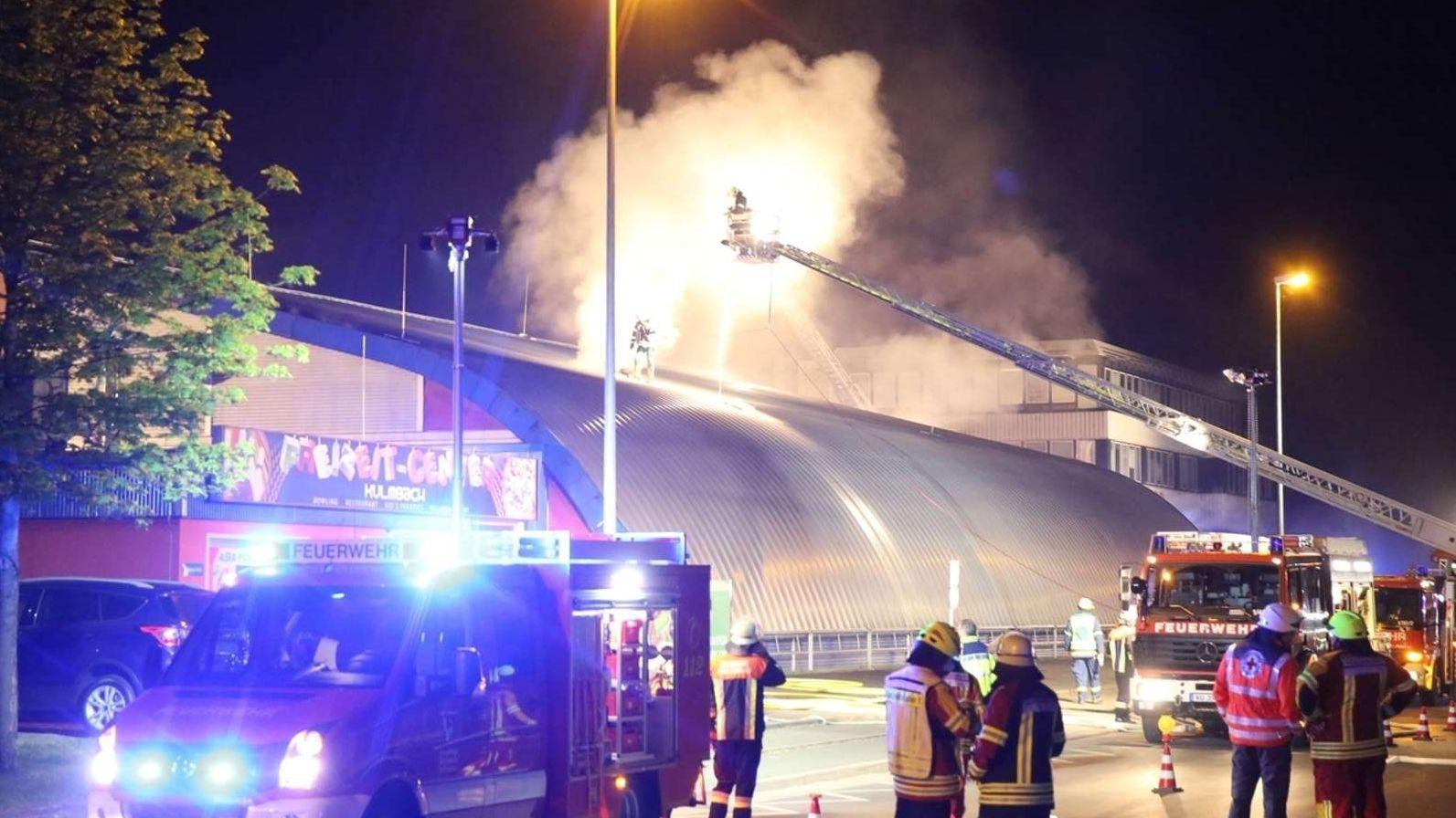 Eine Halle brennt, Feuerwehrleute sind bei Löscharbeiten zu sehen.
