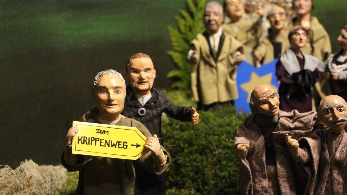 """Krippen-Figuren halten ein Schild hoch auf dem """"Zum Krippenweg"""" steht."""