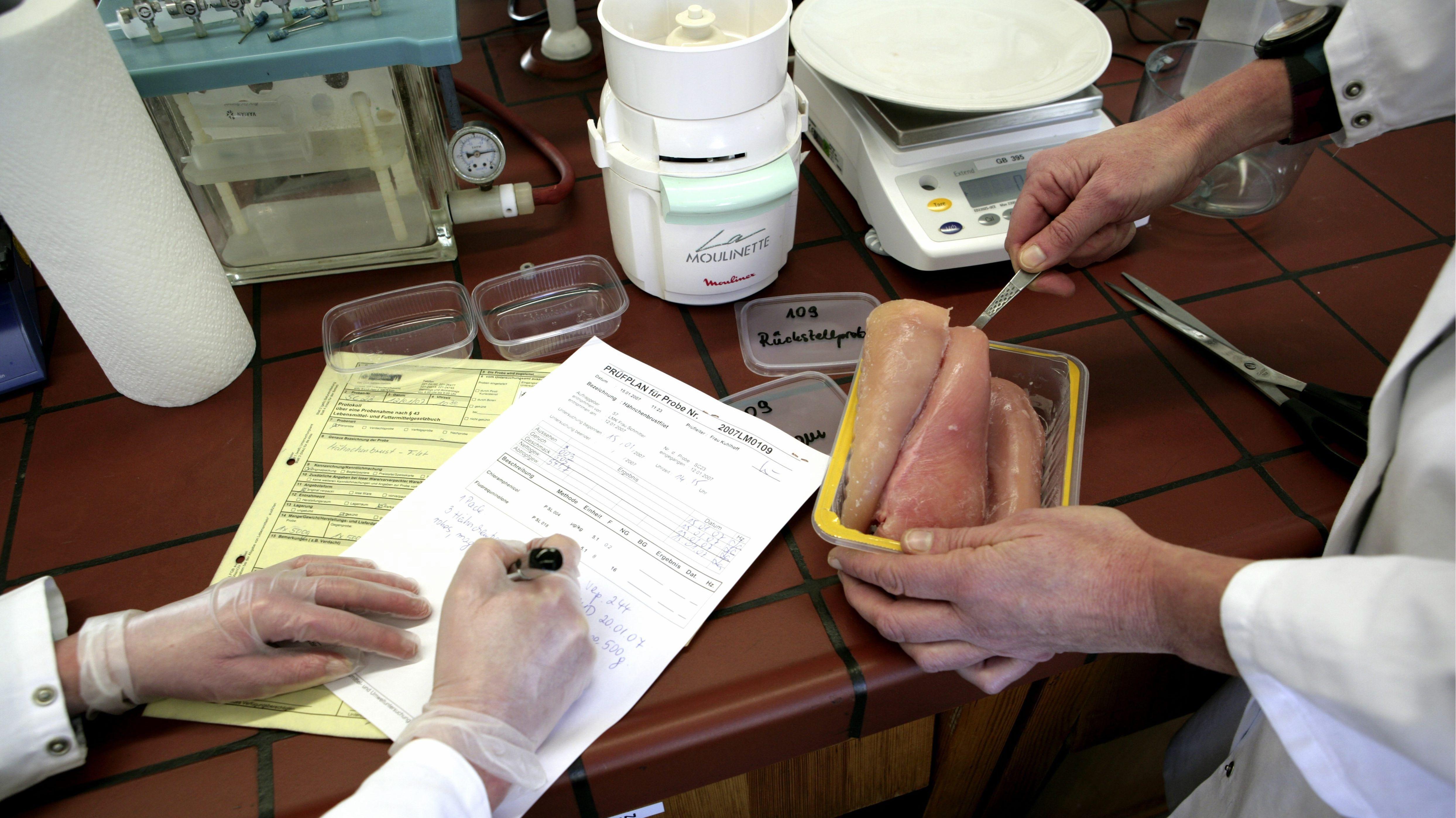 Kontrolleure untersuchen Geflügelfleisch im Labor
