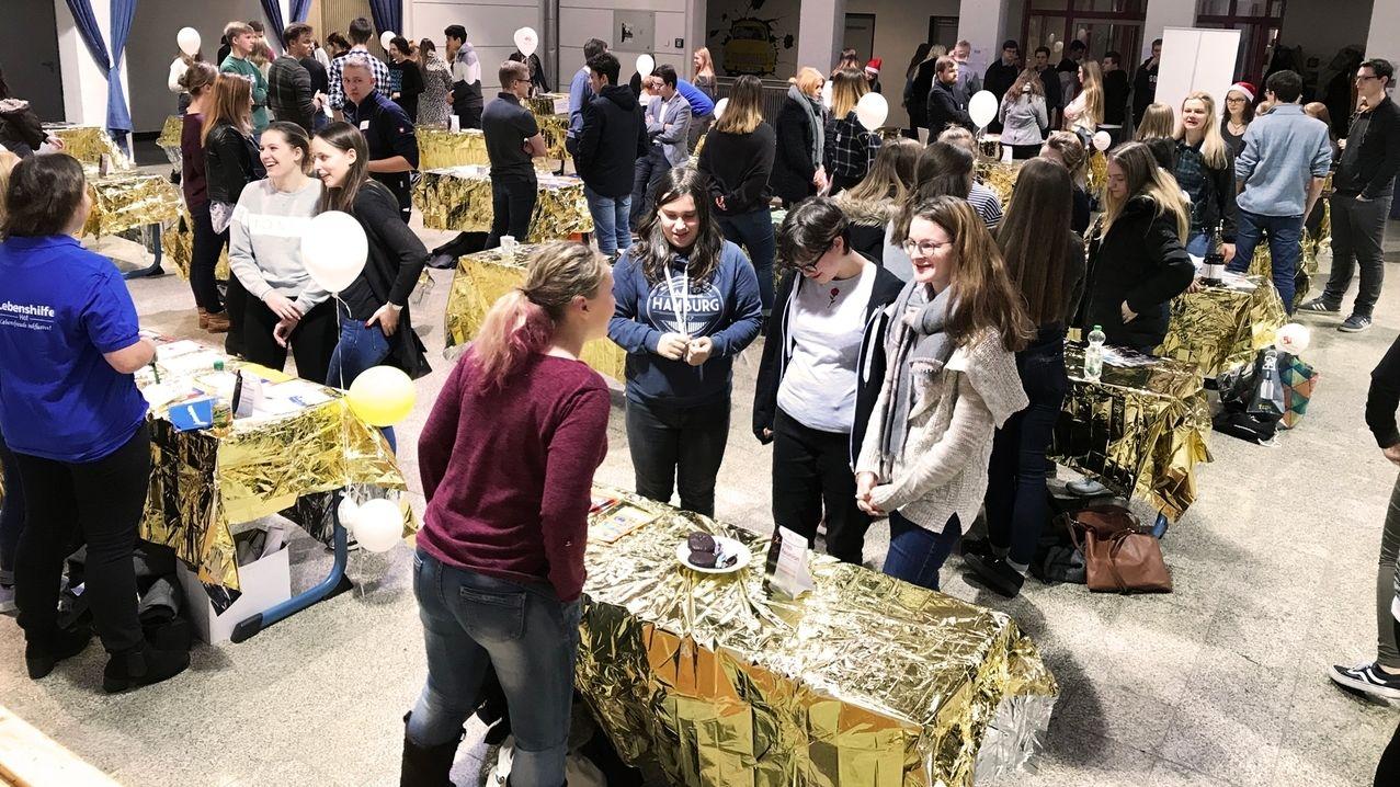 Junge Menschen stehen in einer festlich geschmückten Halle. auf den Tischen liegen goldene Tischdecken.