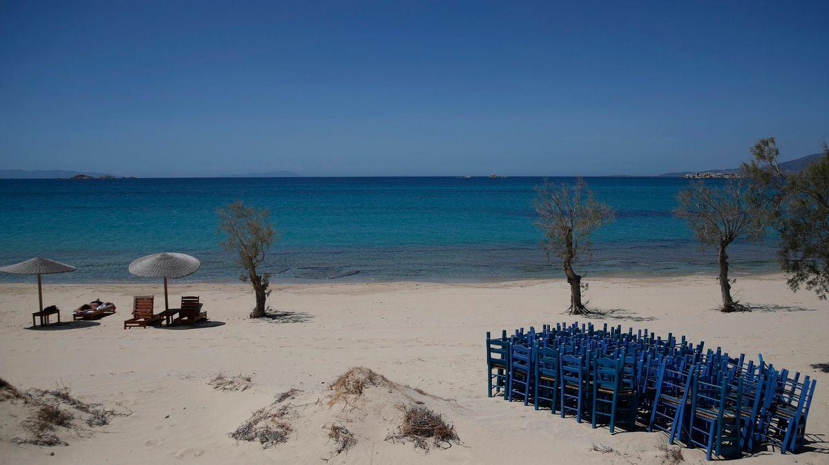 Ein Tourist genießt die Sonne, während Tavernenstühle am Strand von Plaka auf der Ägäisinsel Naxos gelagert werden.