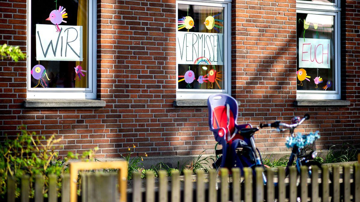 """Plakate mit der Aufschrift """"Wir vermissen euch"""" hängen im Fenster einer Kita in Oldenburg."""