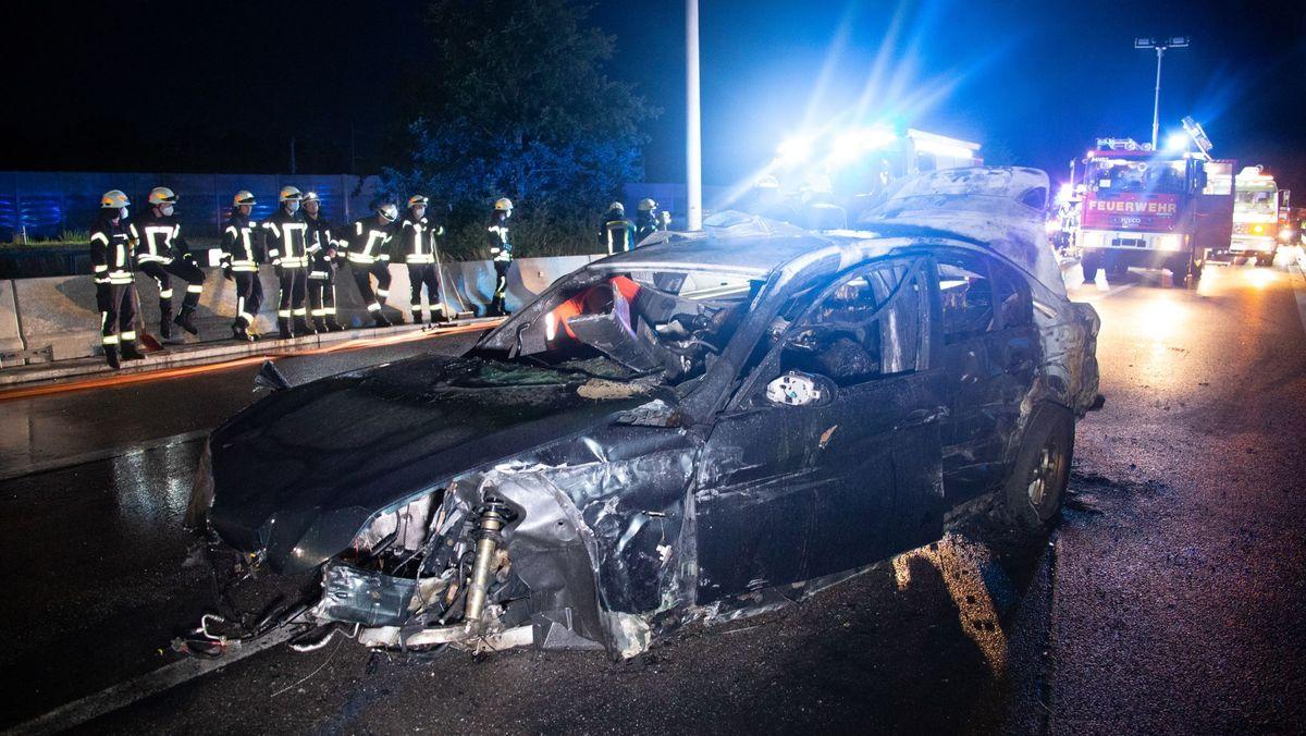Komplett zerstörtes Auto auf der nächtlichen Autobahn, dahinter Feuerwehrleute.