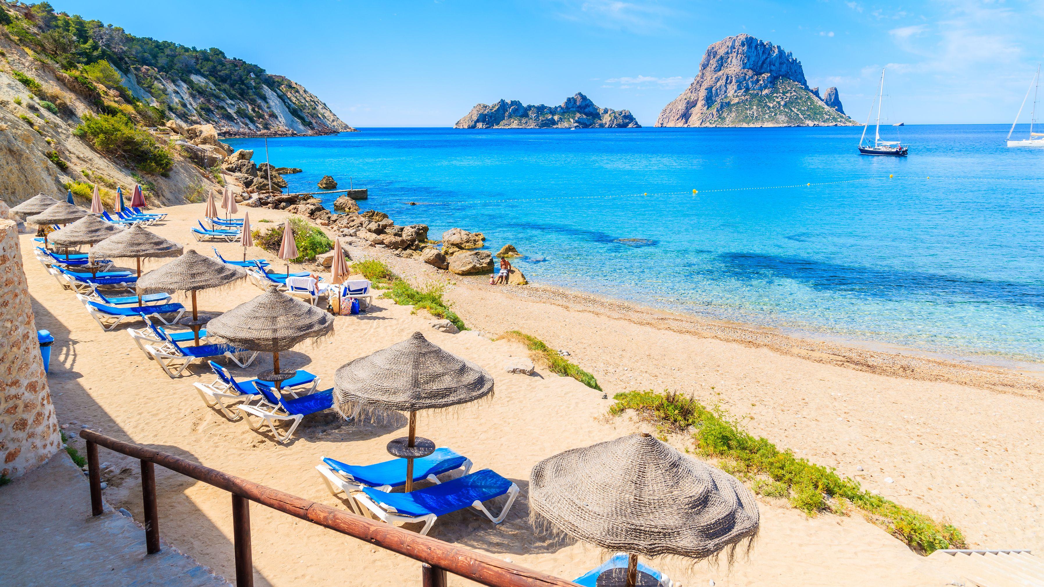 Liegestühle und Sonnenschirmen an einem Sandstrand mit klarem Wasser