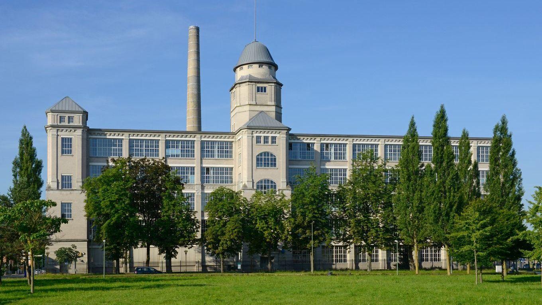Fassade des Glaspalasts Augsburg: Großes Fabrikgebäude mit vielen Fenstern und einem Turm