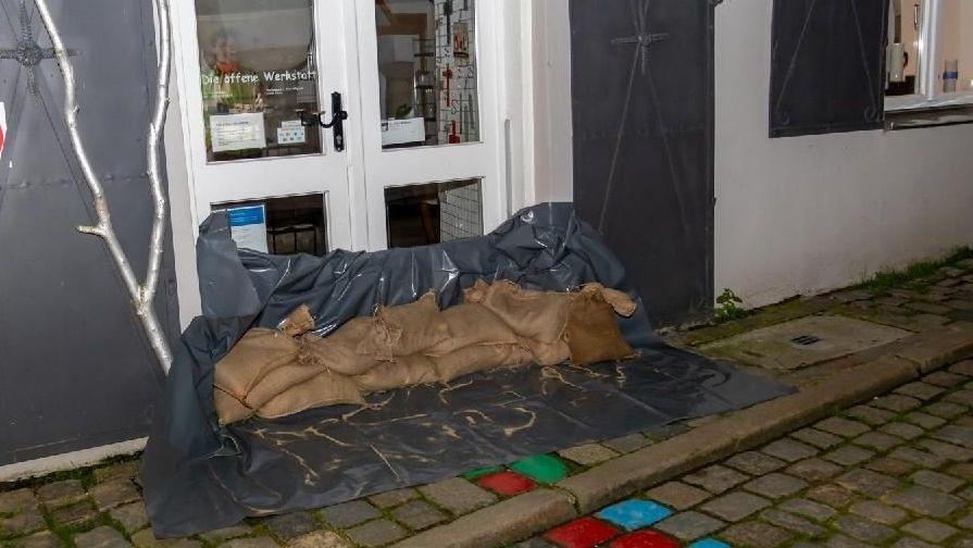 Die Ladentür einer Passauer Werkstatt wurde mit Sandsäcken und Plastikfolie verbarrikadiert