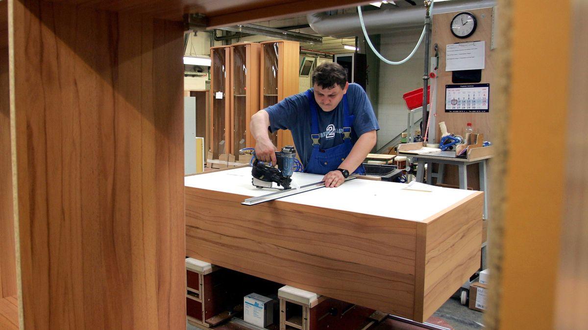 Ein Mitarbeiter stellt einen Holzschrank her.