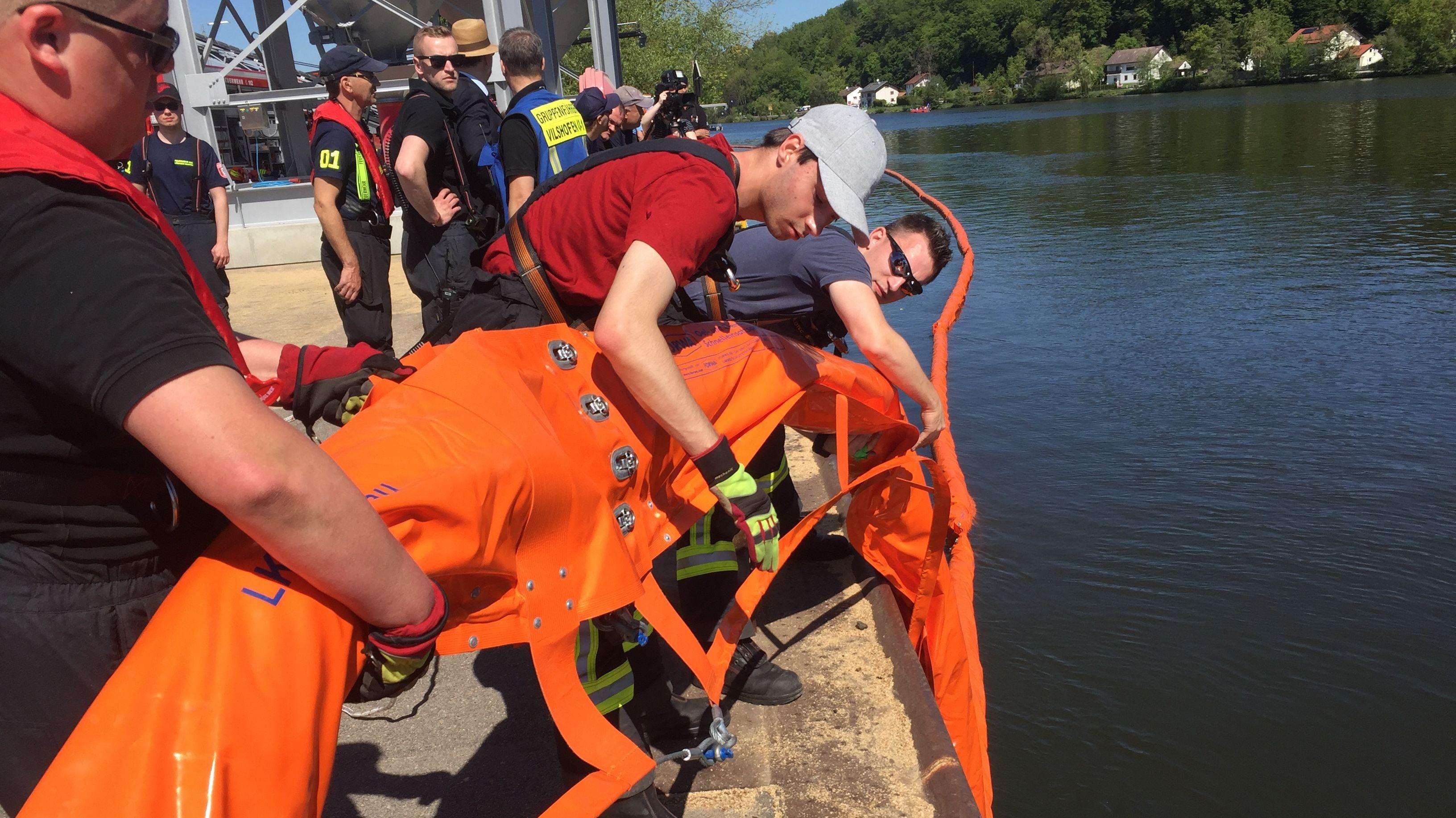Einsatzkräfte lassen Ölsperre zu Wasser.