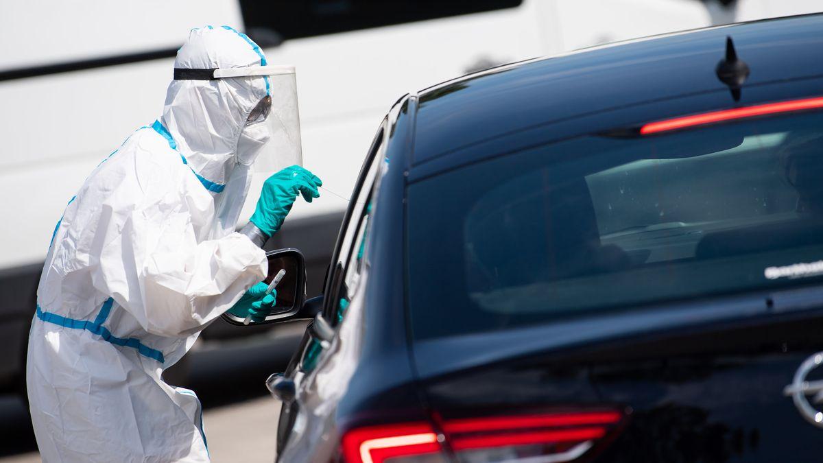 Eine Person mit Schutzanzug nimmt einen Abstrich für einen Corona-Test bei einer Person die sich im Auto befindet.