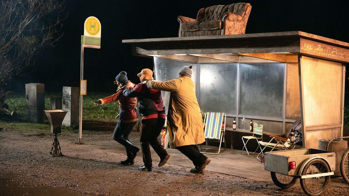 Vor der Bushaltestelle, in der Campingstühle, Tisch und Bier stehen, tanzen drei Gestalten Polonaise.