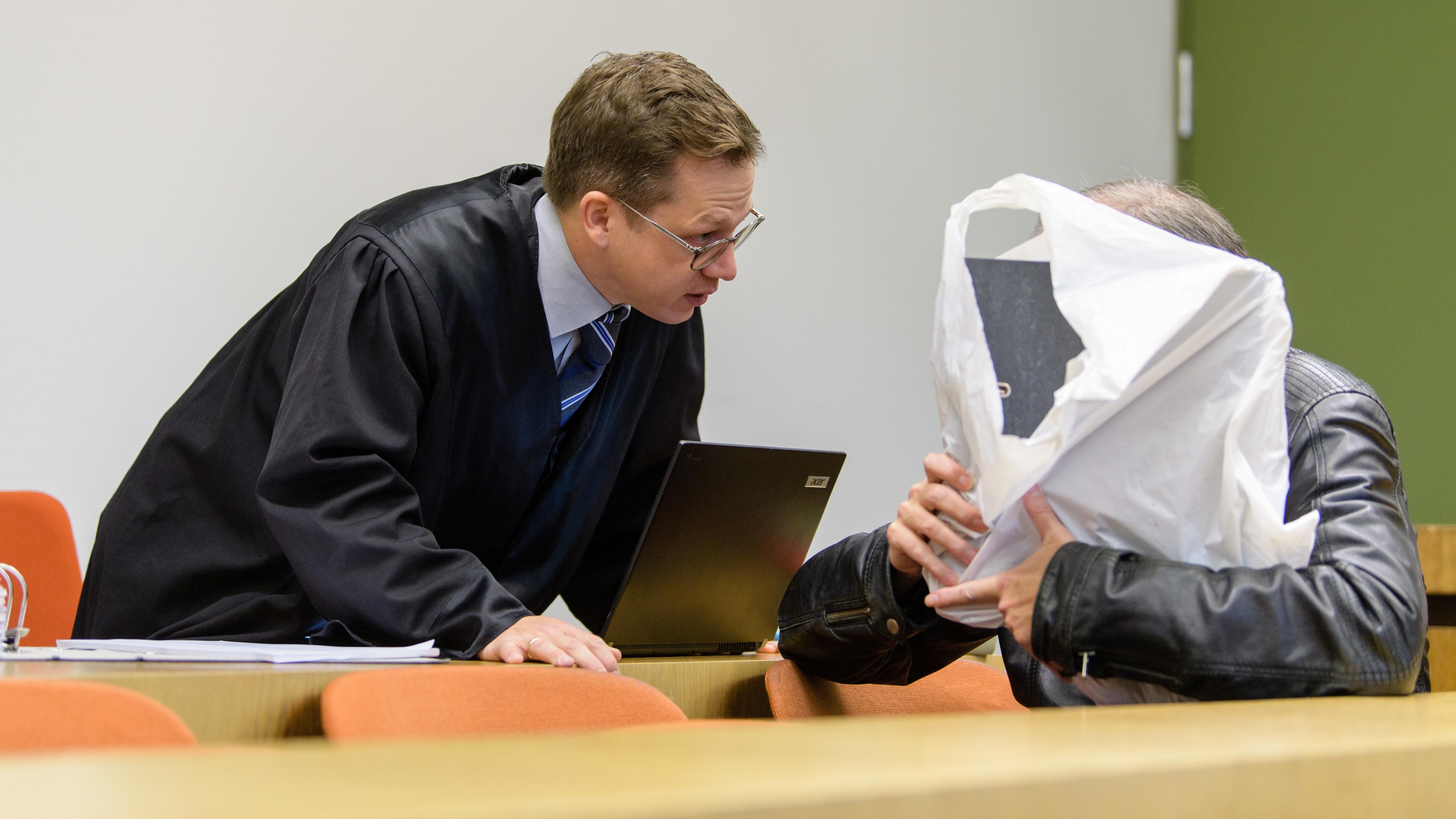 München: Ein wegen millionenschweren Betrugs und Hochstaplerei angeklagter Mann unterhält sich vor seinem Prozess mit seinem Rechtsanwalt.