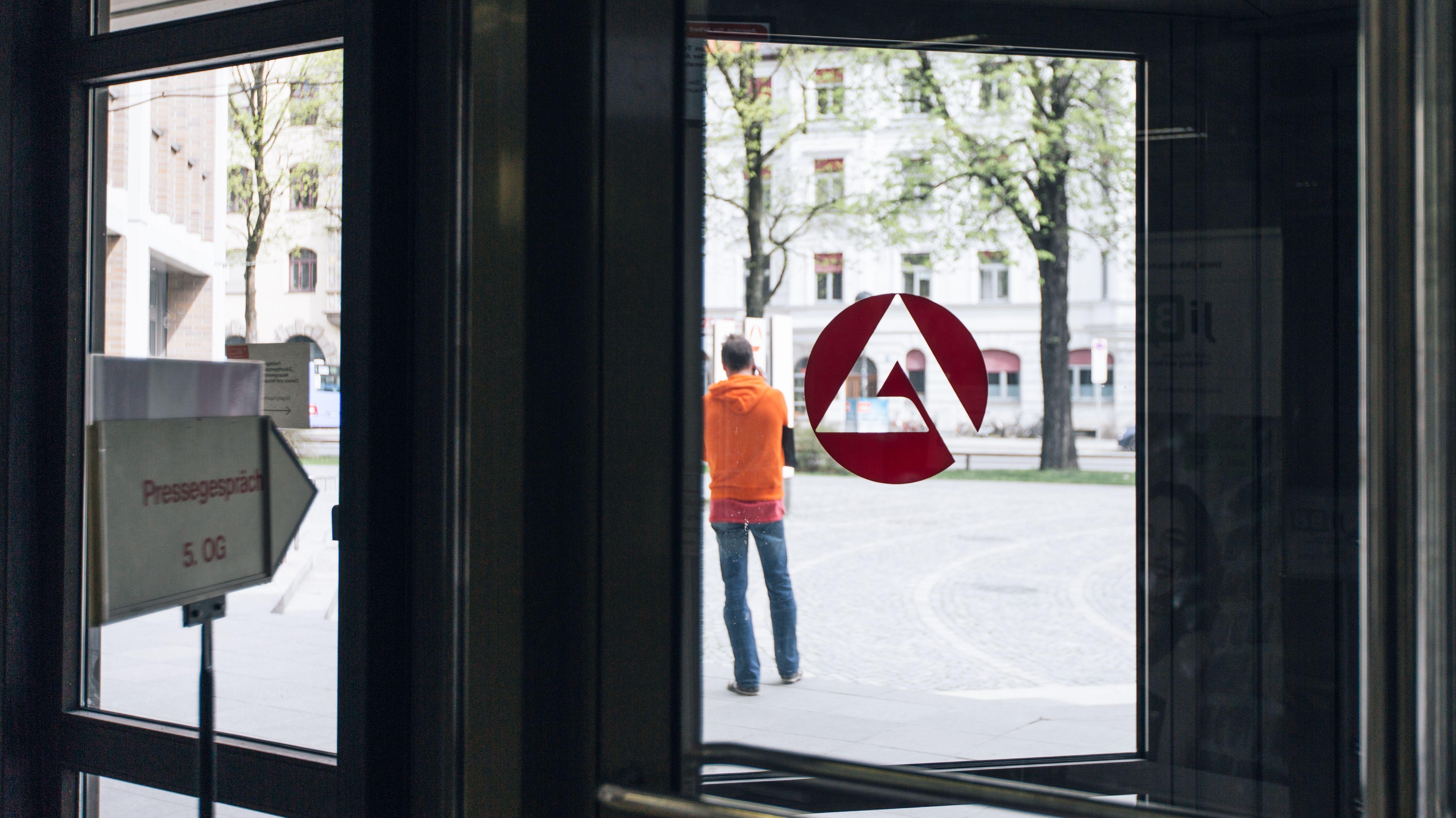 Ein Mann steht vor einer Agentur für Arbeit