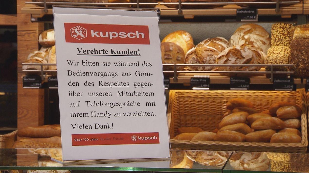 Schild an einer Brot-Theke, auf dem darum gebeten wird, dass Kunden während des Bedienvorgangs aufs Handy verzichten.