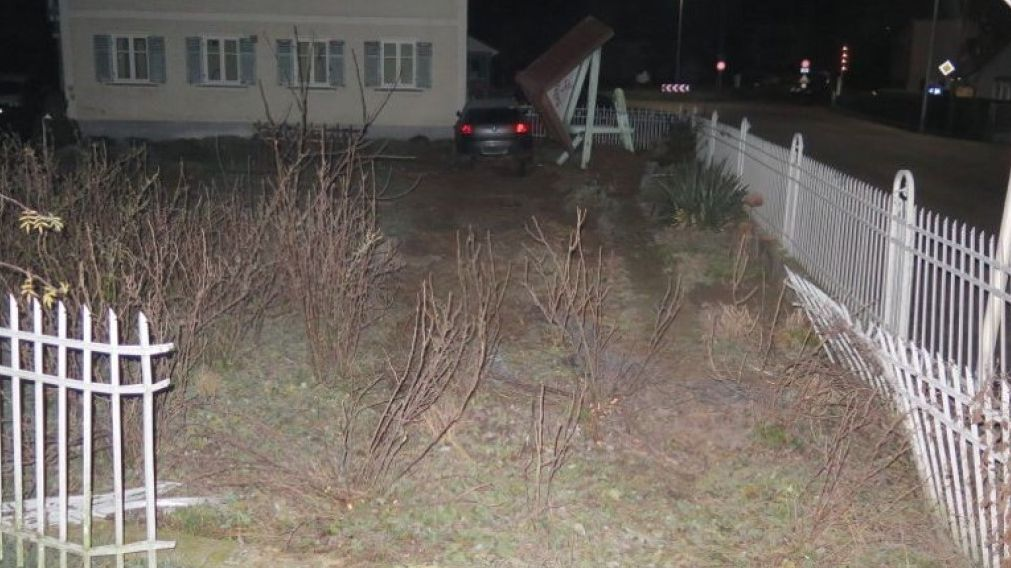 Ein durchbrochener Gartenzaun und ein Auto das im Bereich eines Hausecks steht
