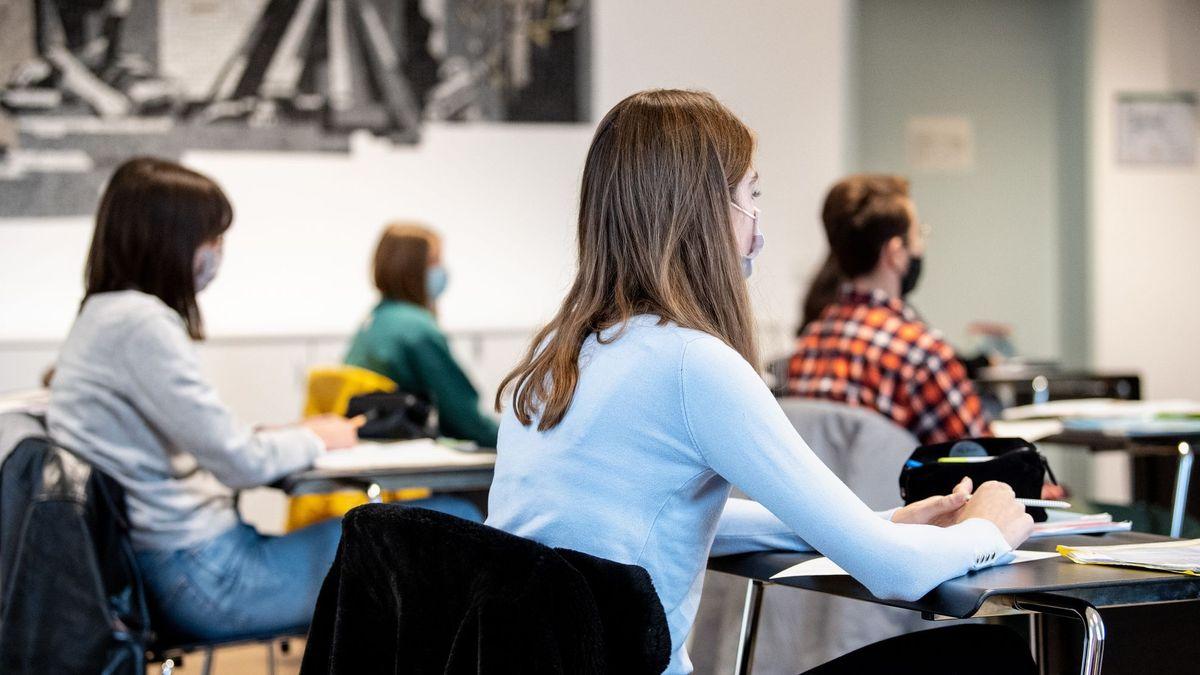 Junge Frauen und Männer sitzen mit Abstand und Maske in einem Unterrichtsraum (Symbolbild)