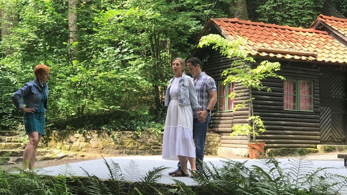 Rita-Lucia Schneider, Regisseurin, Anna Voshege, Sopranistin, und Martin Shalita, Tenor, stehen auf einer Bühne, dahinter ein Blockhaus und Bäume.