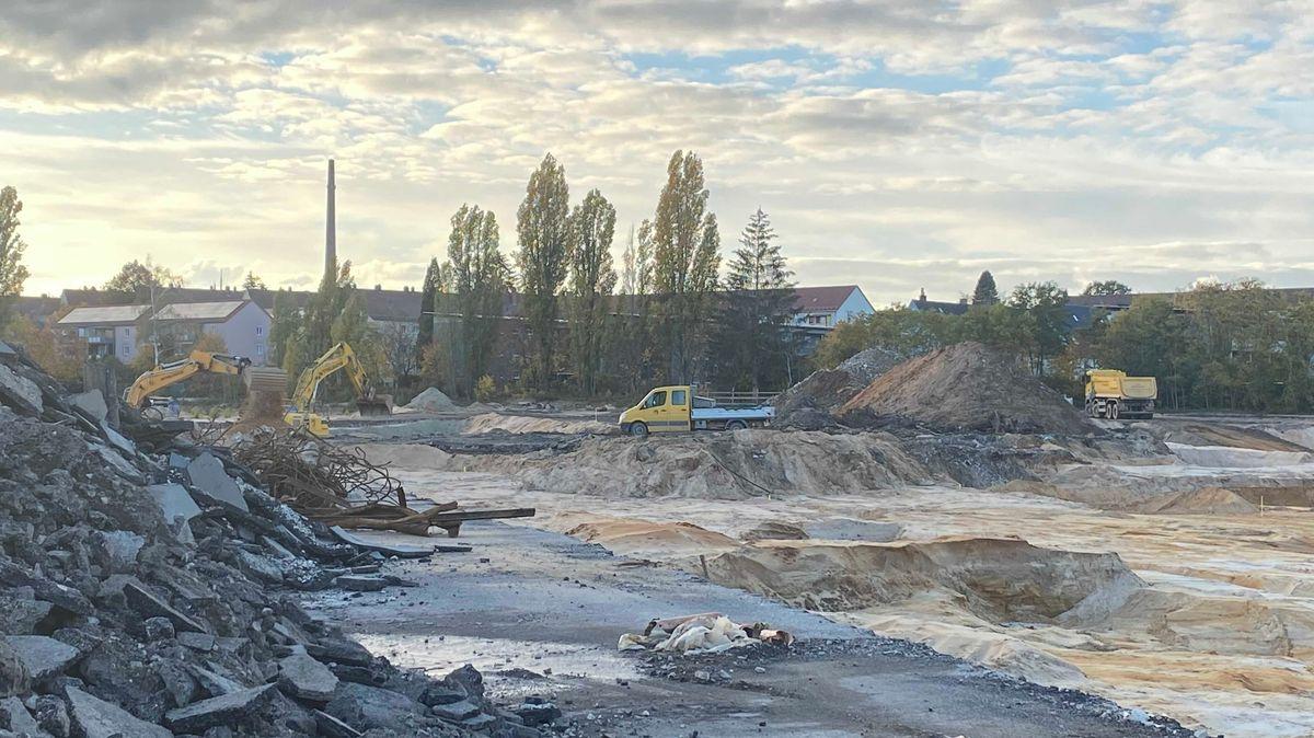 Schuttberg und Baugrube, in der Ferne Bäume, Bagger und Baumaschinen