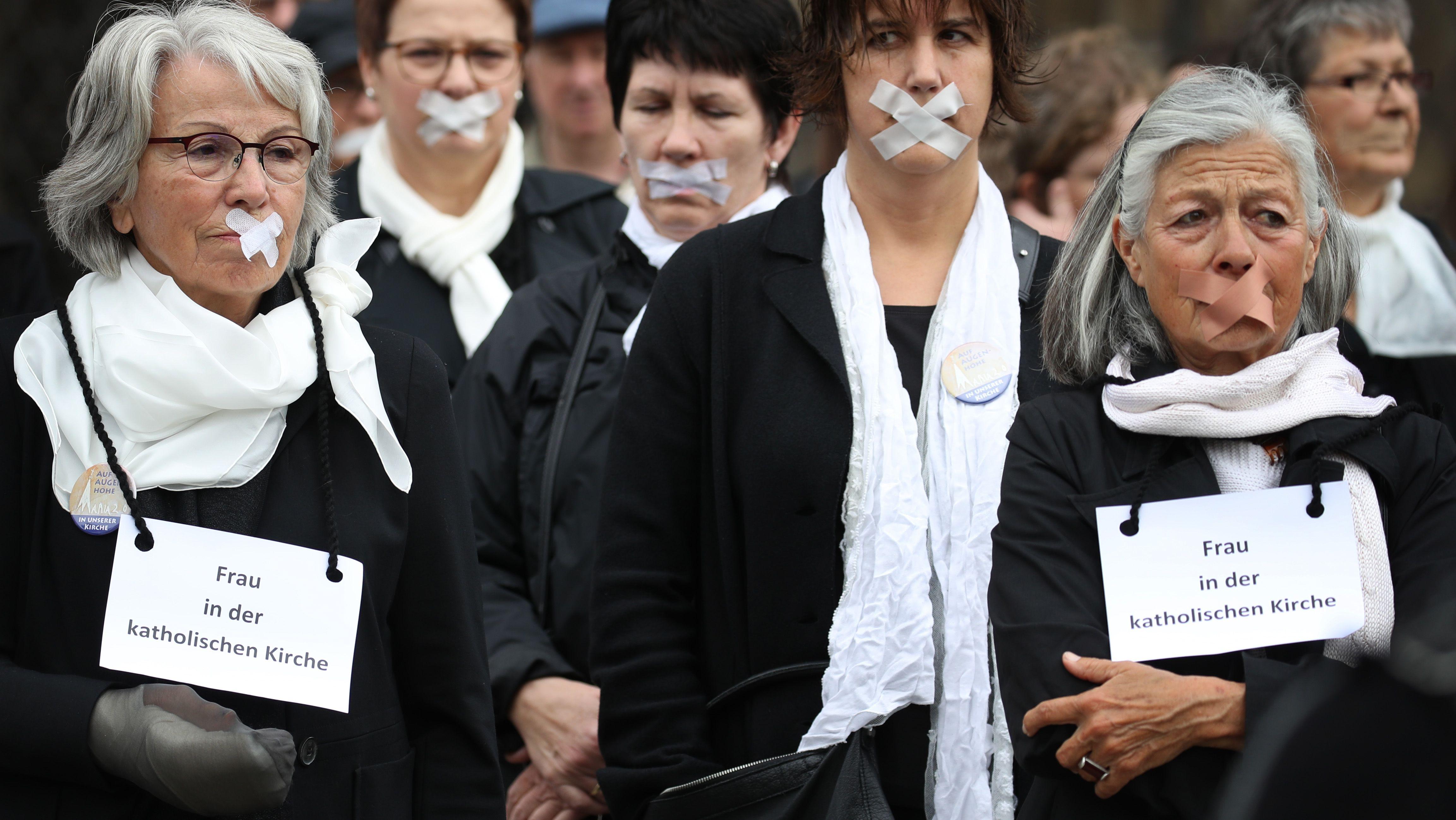 Frauen mit Pflastern über ihren Mündern stehen vor dem Ulmer Münster.