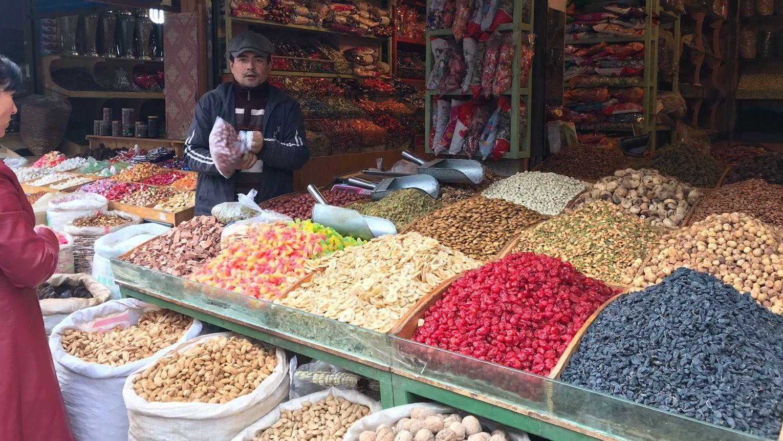 Ein Verkäufer steht vor seinem Laden. Auf einer Auslage türmen sich in Bergen verschiedene getrocknete Früchte.