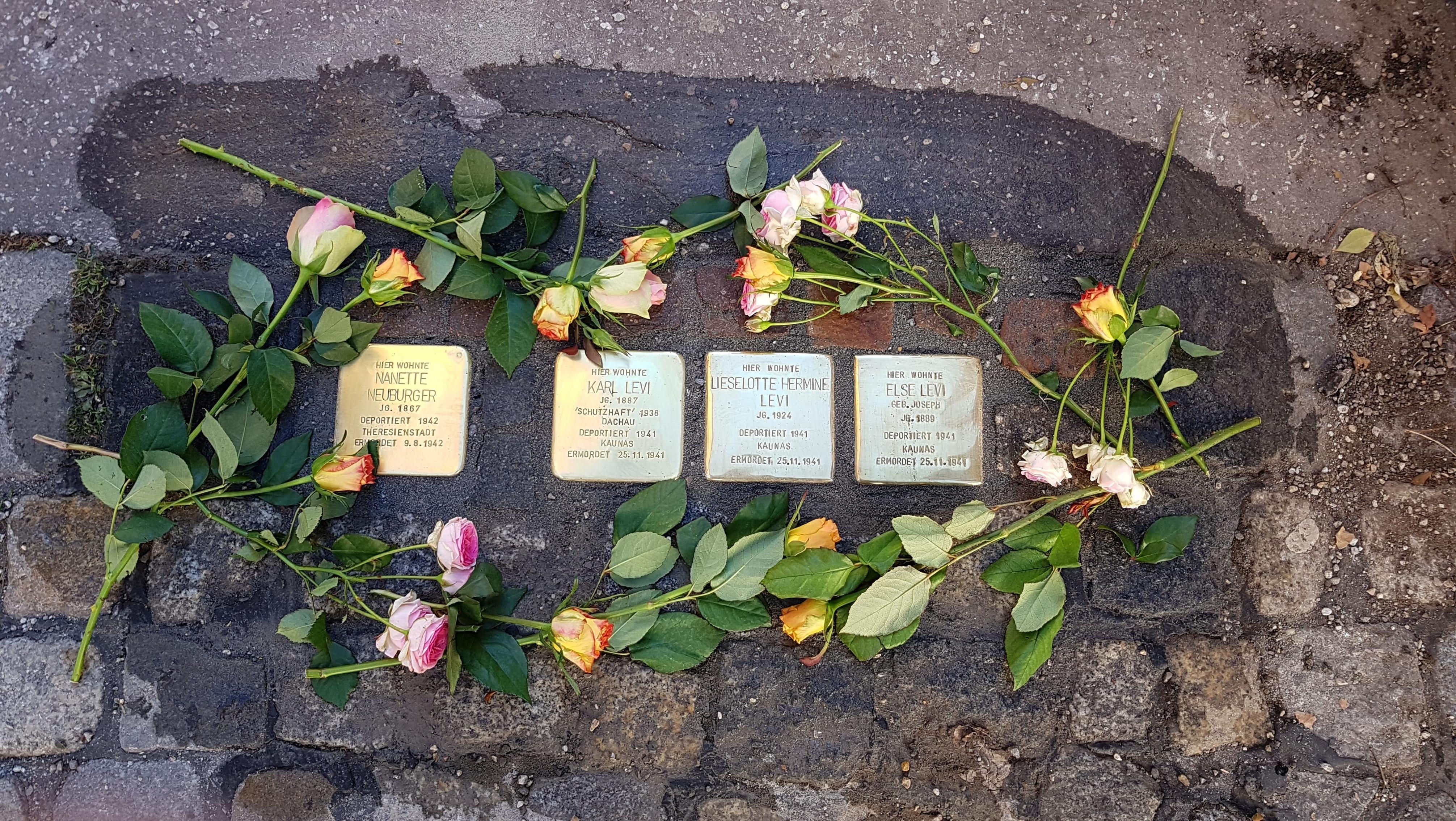 Blumen liegen um neu verlegte Stolpersteine