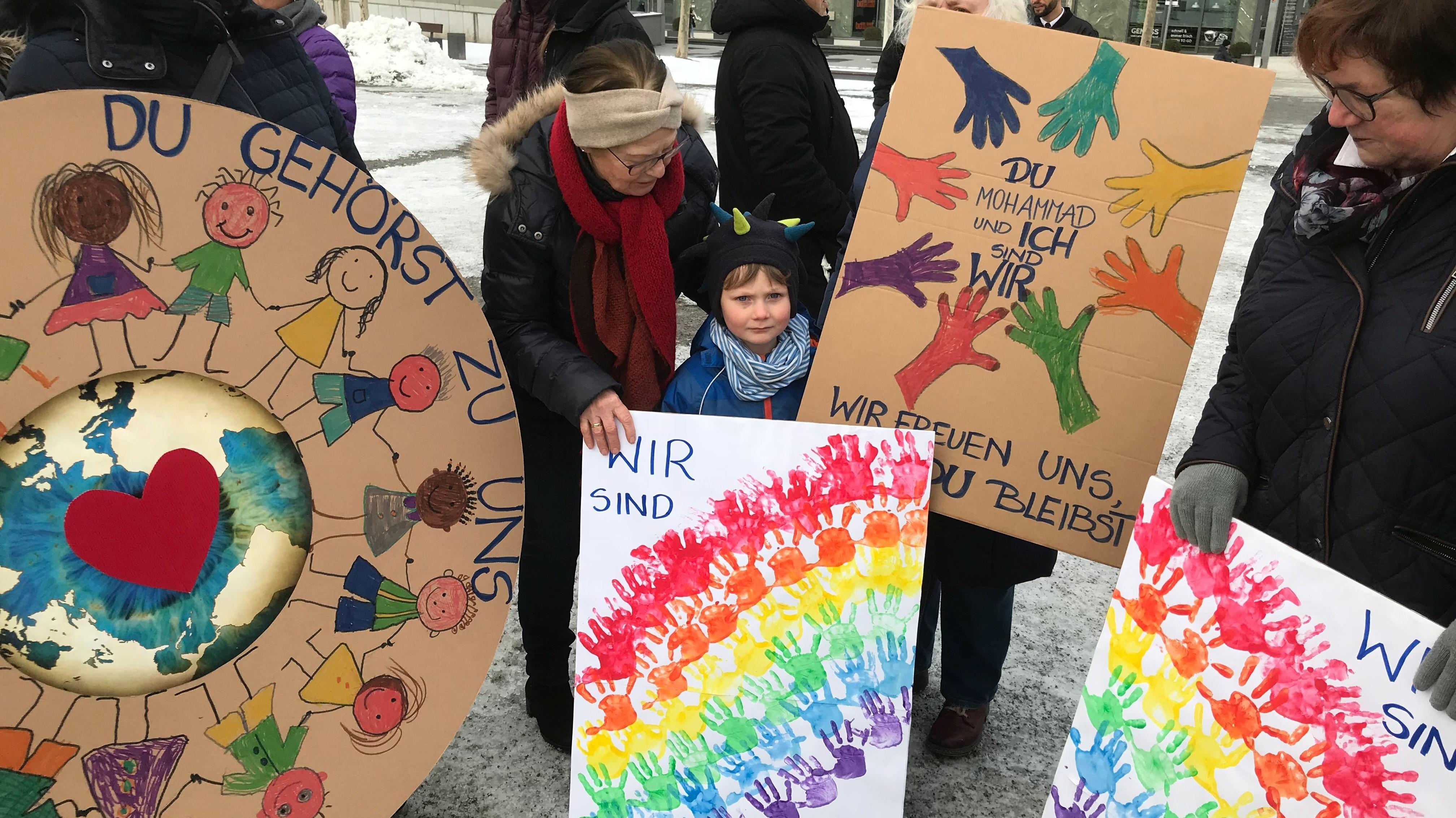 Die Demonstranten haben bunte Plakate gemalt, um auf die Situation der syrischen Familie aufmerksam zu machen