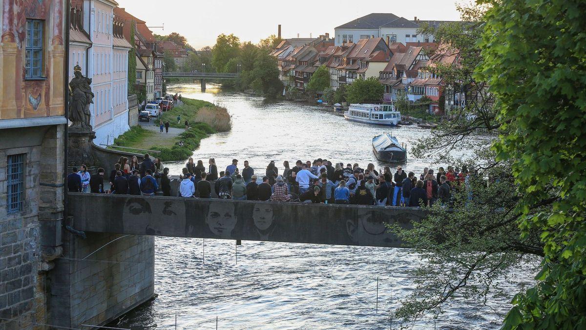 Blick auf die Untere Brücke in Bamberg, auf der sich zahlreiche Menschen versammelt haben.