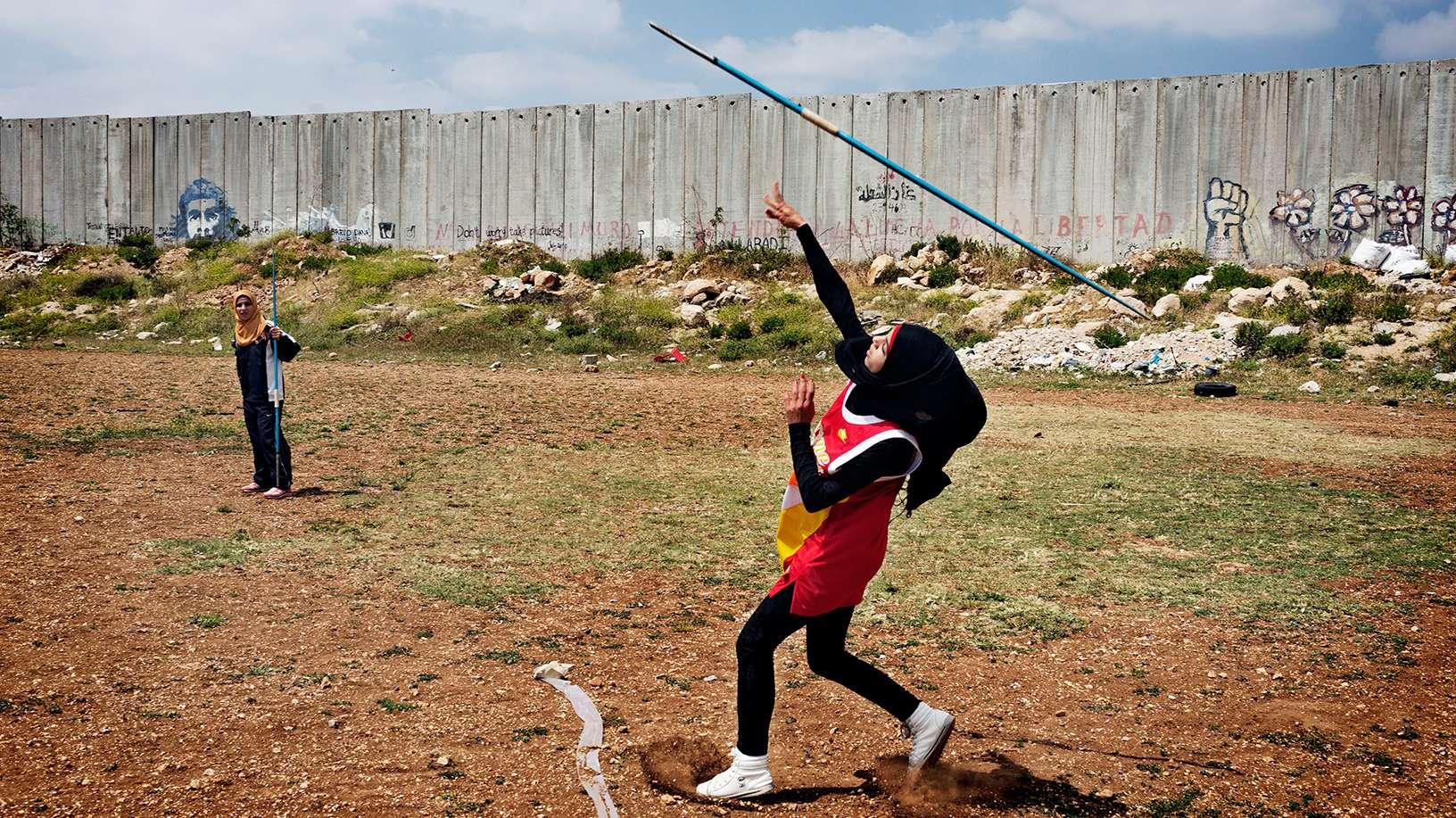 Frau in Sportbekleidung mit Kopftuch wirft einen Speer.