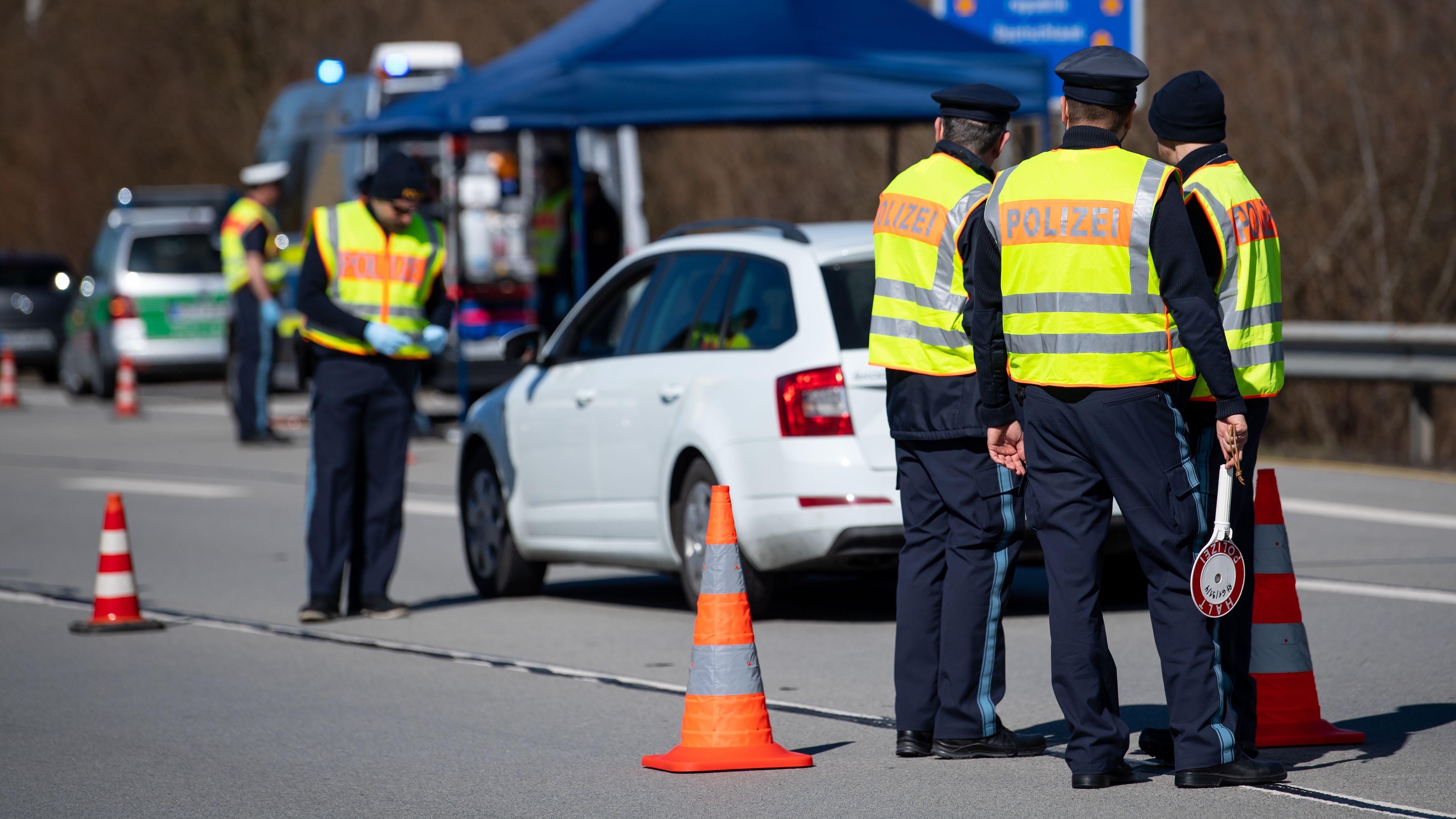 Polizisten stehen an der Bundesstraße 12 in der Nähe von Kirchdorf am Inn an einer Kontrollstelle an der Grenze zu Österreich.