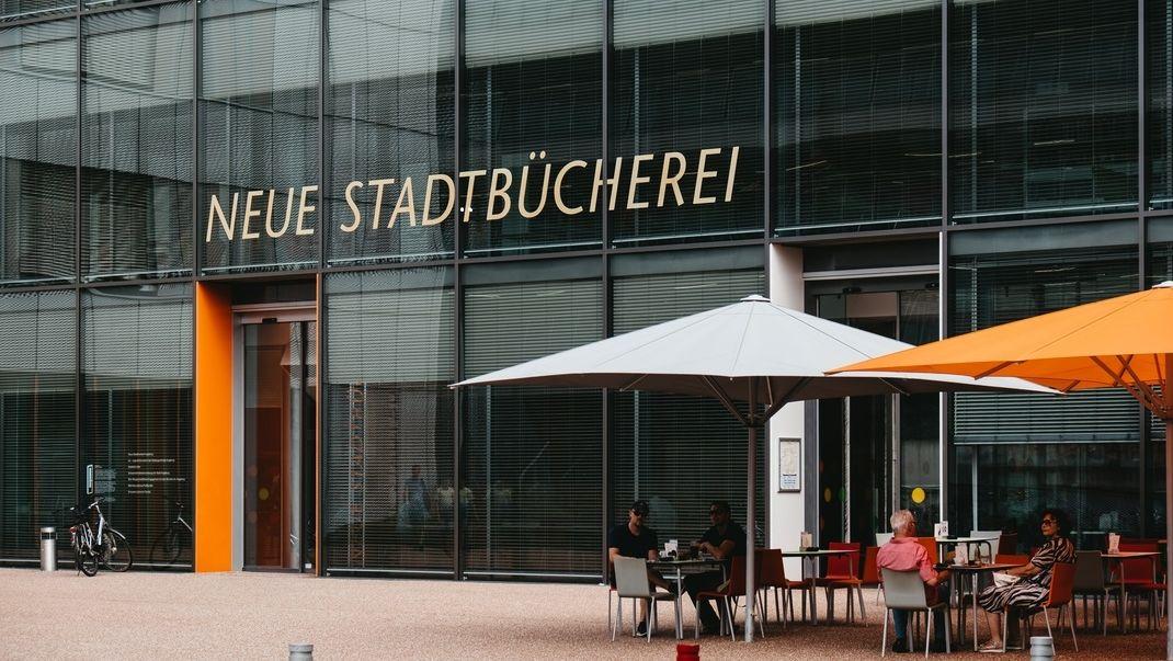 Vor dem Eingang in ein gläsernes Gebäude stehen Tische und Sonnenschirme, an denen ein paar Passanten sitzen: Eingang der Stadtbibliothek Augsburg