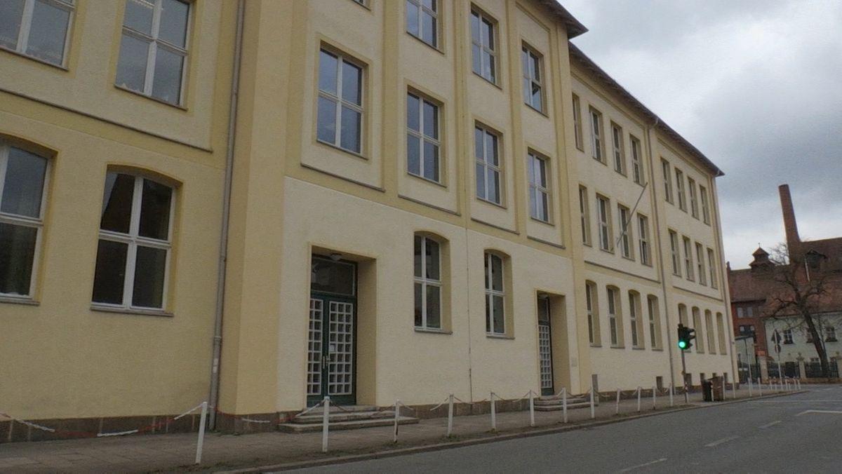Die gelb-weiße Fassade eines Schulhauses, davor eine Straße.