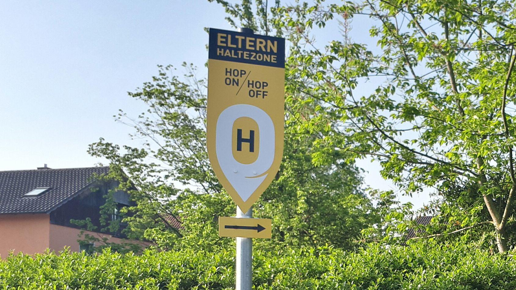 """Ein schwarz-gelbes  Schild mit der Aufschrift: """"Eltern Haltezone"""""""