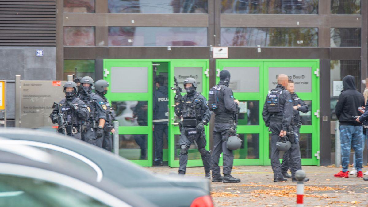 Spezialeinsatzkräfte der Polizei in Schutzmontur vor dem Eingang einer Schule.